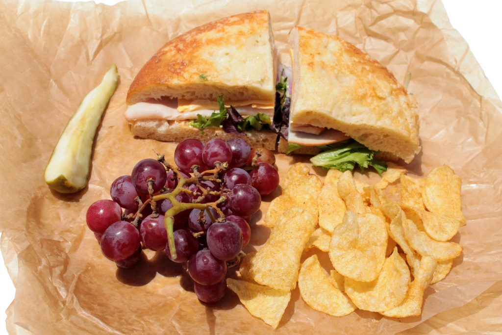 picnic on sandwiches, fruit and chips